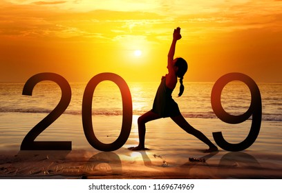 Happy new year card 2019. Silhouette of healthy girl doing Yoga warrior I pose on tropical beach with sunset sky background, practicing yoga on the beach, standing as a part of the Number 2019 sign.