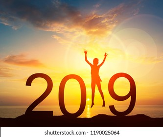 Happy new year card 2019. Silhouette of young girl jump on top of mountain with fantastic sea and sunrise sky. Happy joyful girl jumping as a part of the Number 2019 sign with rising sun background.
