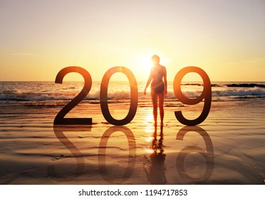 Happy new year card 2019. Silhouette of healthy young woman standing on the beach watching sunset or sunrise, girl in swimming suit looking the rising sun. Concept for women's health 2019 sign.