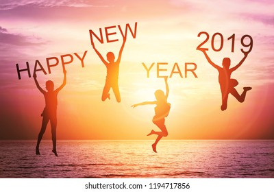 Happy new year card 2019. Silhouette of children girl jump on tropical beach with fantastic sunset sky background. Kids holding the word happy new year and number 2019 with sea and sunrise background.