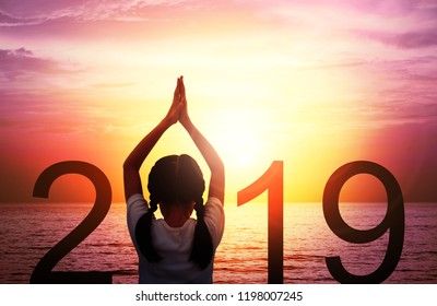 Happy new year card 2019. Silhouette of girl doing Yoga vrikshasana tree pose on tropical beach with fantastic sunset sky background. Kid standing as part of the Number 2019 sign and watching sunrise.