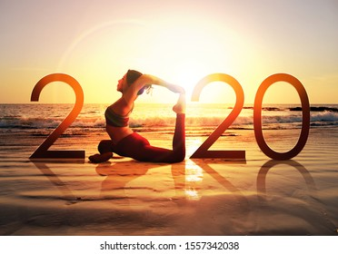Happy new year card 2020. Silhouette of healthy girl doing Yoga One Legged Pigeon pose on tropical beach with sunset sky background, woman practicing yoga as a part of the Number 2020 sign.