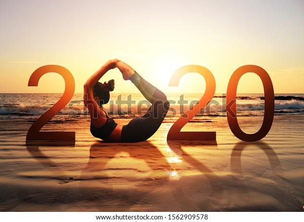 Gute neue Jahreskarte 2020. Silhouette von gesunden Mädchen mit Yoga Bow Pose auf tropischen Strand mit Sonnenuntergang Himmel Hintergrund, Frau, die Yoga als Teil der Nummer 2020 Zeichen.