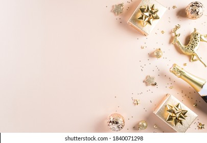 Happy New year celebration background concept. Golden gift box, stars, christmas ball and champagne on pastel background. Flat lay, top view with copy space.