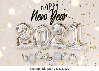 Happy New Year celebration. Silver foil balloons numeral 2021, party decoration and confetti stars on beige background.