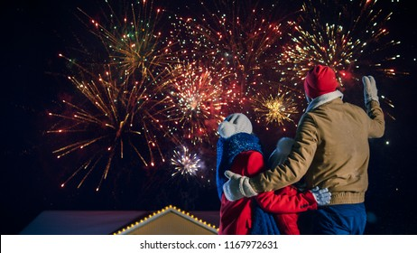 Happy New Year Celebration, Young Family of Three Standing in the Front Yard Watching Beautiful Fireworks. In the Evening while Snow is Falling Father, Mother and Cute Little Daughter Look up.