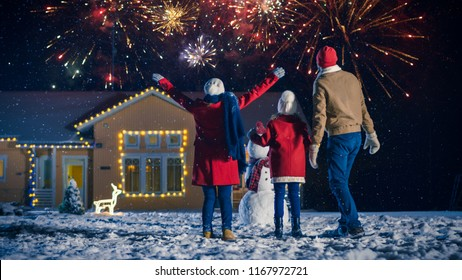 Happy New Year Celebration, Young Family of Three Standing in the Front Yard Looking into the Sky In the Eveningю House Decorated with Garlands for Christmas Eve.