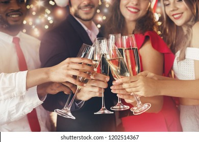Happy New Year. Cheerful people clinking with champagne flutes, close up