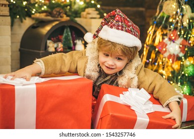 Happy new year. Child with big gift box. Christmas child holding a huge gift box. Little Santa Claus gifting gift. Cheerful cute child opening a Christmas present