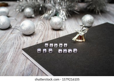 Happy New Year and Christmas! Christmas balls, abbreviation, letters, bell, book on a wooden white table. View from above