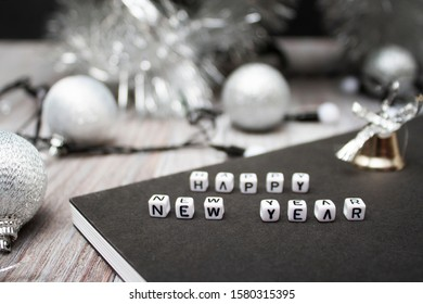 Happy New Year and Christmas! Christmas balls, abbreviation, letters, bell, garland, book on a wooden white table. View from above.