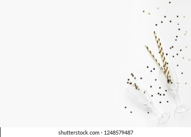 Happy New Year composition. Champagne glasses with gold confetti stars and drinking straws on white table background. Party concept. Flat lay, top view.