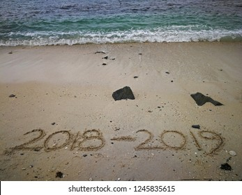 happy new year concept 2018 to 2019 written in the sand on a beach