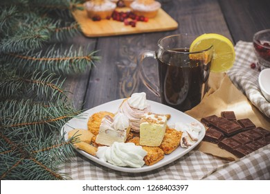 Happy New Year fir branches decorated with gingerbread stars, cinnamon sticks, dried orange slices and meringue peaks, bright cranberries, sweets in a dessert plate, a broken chocolate bar on kraft pa