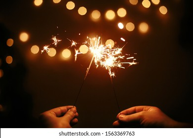 Happy New Year. Glowing sparklers in couple hands on background of golden christmas tree lights, family celebrating in dark festive room. Space for text. Fireworks burning in hands. Happy Holidays