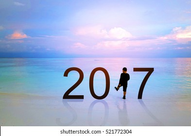 happy new year greeting card 2017 silhouette of a boy playing and walking on tropical