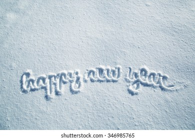Happy new year handwritten word message on the snow with copy space background.