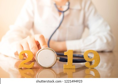 Happy New Year for health care and medical concept. Doctor in white uniform holding stethoscope near gold wooden number 2019 on doctor desk. Idea for new trend in medicine treatment and diagnosis.