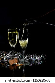 Happy New Year image with two glasses of sparkling champagne and holiday decorations on a black background. Champagne is being poured into one glass.