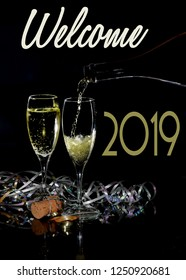 Happy New Year image with two glasses of sparkling champagne and holiday decorations on a black background. Champagne is being poured into one glass. 2019 text added.