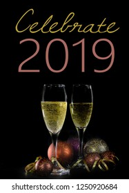 Happy New Year image with two glasses of sparkling champagne and holiday decorations on a black background. Text for 2019 added.