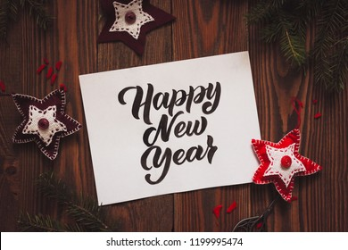 Happy new year lettering inscription on paper on wooden background with handmade toys.