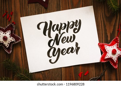 Happy New Year lettering on a white sheet of paper on a wooden background, with handmade Christmas toys made of felt and fir branches. Top view, close-up and rustic style concept.