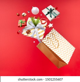 Happy New year magic concept. Christmas paper shopping bag, gifts, Lollipop, decorations and toys are flying in the air on a red background. Winter sale.