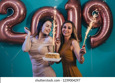 Happy new year and Merry Christmas Beautiful young women celebrating with cake and burning candles