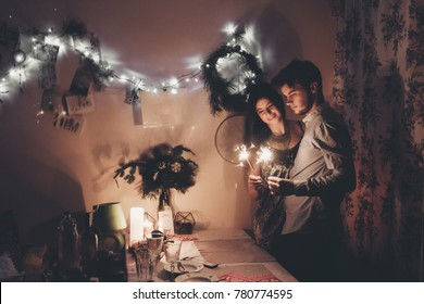 happy new year and merry christmas concept. happy stylish hipster couple holding burning sparklers fireworks and embracing in room at hoome in evening. happy holidays. toned