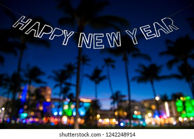 Happy New Year message hanging in glittery party bunting above tropical palm trees of the glowing neon lights of the skyline of Miami Beach, Florida, USA