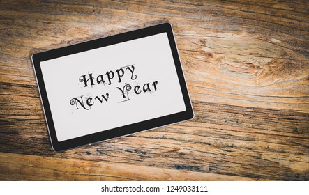 Happy New Year on white tablet screen. Rustic wooden backgrounds.