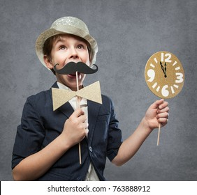 Happy New Year Series, with a 7 year olf happy Boy, holding several Photo Booth Items, while having fun. With Clock minutes before midnight against grey concrete Background