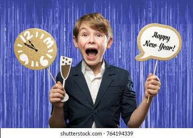 Happy New Year Series, with a 7 year olf happy Boy, holding several Photo Booth Items, while having fun. With Clock minutes before midnight against Blue/Purple Tinsel Background
