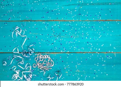 Happy New Year sign with holiday confetti and ribbon border on blank antique rustic teal blue textured wood background; color copy space for text with pink, purple, blue decorations