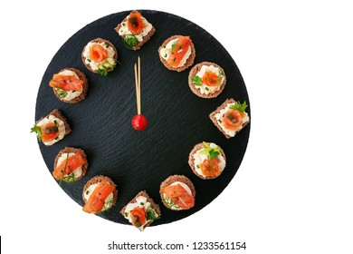Happy New Year! Smoked salmon canapes on black slate platter form a clock face showing midnight.