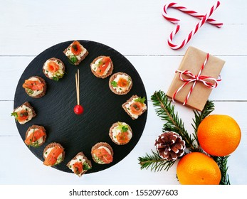 Happy New Year! Smoked salmon canapes on black slate platter form a clock face showing midnight. Flat lay gift, candy cane, oranges and fir branches decorate the white wooden table.