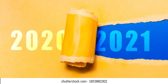 Happy new year, new start, new page of life; resolution concept. Text of 2021 on blue background in hole of torn yellow textured paper with text of 2020. - Shutterstock ID 1853882302