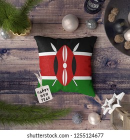 Happy New Year tag with Kenya flag on pillow. Christmas decoration concept on wooden table with lovely objects.