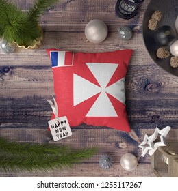 Happy New Year tag with Wallis and Futuna flag on pillow. Christmas decoration concept on wooden table with lovely objects.