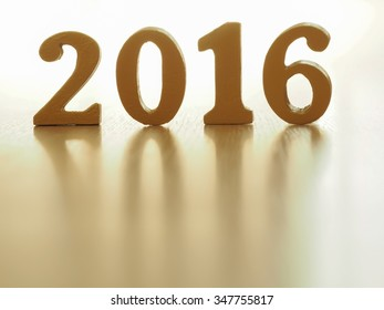 Happy new year text of gold 2016 make from wood on wood floor. New year decoration.