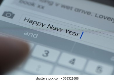 Happy New year text message on mobile phone with finger typing