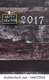 Happy New Year text on black board with number 2017 on dark wooden background. Empty space for text.
