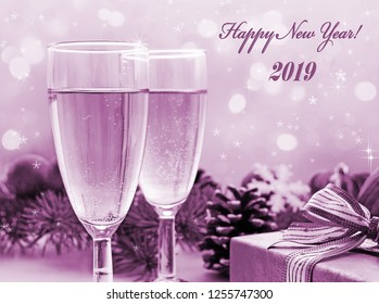 Happy New Year! Two glasses of champagne, gift and Christmas decorations, holiday background, purple tint