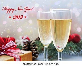 Happy New Year! Two glasses of champagne, gift and Christmas decorations, holiday background.