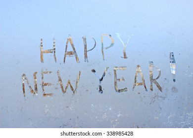 """happy new year"" -  written on frosty winter window background"