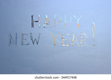 """happy new year"" written on frosty winter window background."