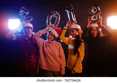Happy New Year to you! Group of cheerful young people in Santa hats carrying silver colored numbers