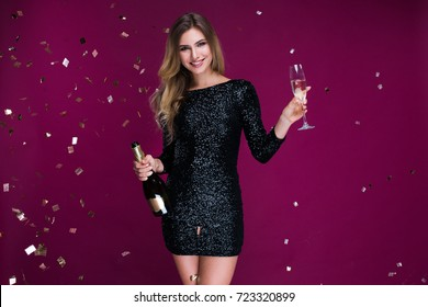 Happy New Year to you! One beautiful young woman with confetti, celebration Christmas with bottle and glass of champagne. New Year's party. Christmas Eve.