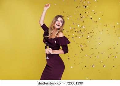 Happy New Year to you. One young and beautiful woman dancing with glass of champagne and smiling. Girl is happy about the New Year